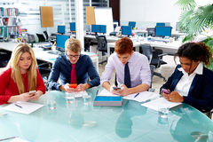 Executivos da equipe que joga smartphones Foto de Stock