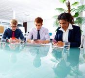Executivos da equipe que joga smartphones Imagens de Stock Royalty Free