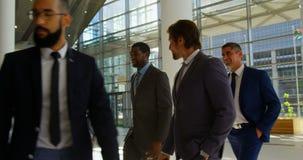 executivos da Misturado-raça que andam junto na entrada no escritório 4k filme