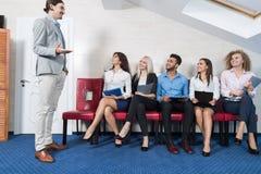 Executivos da reunião de grupo que senta-se na linha fila, recrutamento Job Interview Candidate de espera dos empresários fotografia de stock royalty free