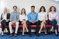 Executivos da reunião de grupo que senta-se na linha fila, recrutamento Job Interview de espera da multidão dos empresários Fotografia de Stock Royalty Free