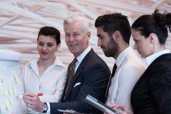 Executivos da sessão de reflexão do grupo e as notas da tomada a flipboar Imagens de Stock Royalty Free