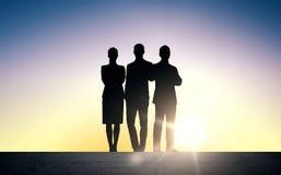 Executivos das silhuetas em escadas sobre o sol Fotografia de Stock