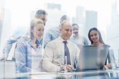 Executivos de sorriso com o portátil no escritório Foto de Stock
