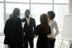 Executivos de sorriso diversos que têm o tog ereto da conversação imagem de stock