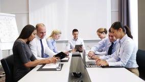 Executivos de sorriso que encontram-se no escritório video estoque