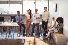 Executivos de sorriso que relaxam no escritório criativo imagens de stock