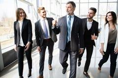 Executivos de Team Walking In Modern Office, homens de negócios seguros e mulheres de negócios com líder maduro In Foreground fotos de stock