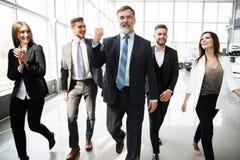 Executivos de Team Walking In Modern Office, homens de neg?cios seguros e mulheres de neg?cios com l?der maduro In Foreground fotografia de stock