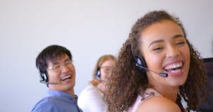 Executivos de vendas multi-étnicos felizes do cliente que falam em auriculares no escritório moderno 4k filme