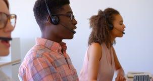 executivos de vendas Multi-?tnicos do cliente que falam em auriculares no escrit?rio moderno 4k video estoque