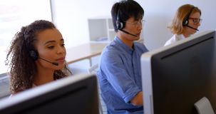 executivos de vendas Multi-?tnicos do cliente que falam em auriculares no escrit?rio moderno 4k vídeos de arquivo