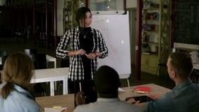 Executivos diversos no seminário que senta-se em um escritório moderno Posição fêmea do líder bonito novo perto do whiteboard vídeos de arquivo
