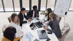 Executivos diversos novos que encontram-se na tabela da sala de reuniões que discute o relatório financeiro usando gráficos e rel video estoque