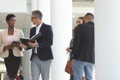 Executivos diversos que interagem um com o otro ao andar no escritório da entrada foto de stock