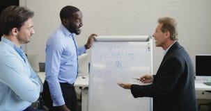 Executivos do grupo que conceitua junto explicando ideias na placa branca durante a reunião da equipe no escritório moderno, mist filme