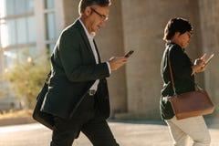 Executivos do telefone celular de utilização ocupado ao andar na rua fotos de stock royalty free