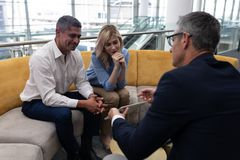 Executivos dos Caucasians que discutem sobre a tabuleta digital no sofá fotografia de stock royalty free