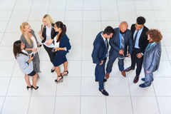 Executivos dos homens e as mulheres do grupo que estão o colega separado Team Communication dos empresários da reunião da discuss imagem de stock