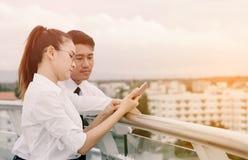 Executivos dos pares que usam o smartphone junto Foto de Stock Royalty Free