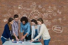 Executivos em uma mesa que apontam uma tabuleta contra a parede de tijolo com gráficos Fotografia de Stock
