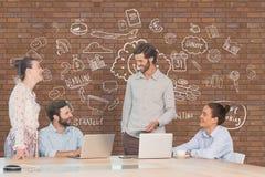 Executivos em uma mesa que falam contra a parede de tijolo com gráficos Imagens de Stock Royalty Free