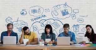 Executivos em uma mesa que olha computadores e tabuletas contra a parede branca com gráficos azuis Imagens de Stock Royalty Free