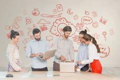 Executivos em uma mesa que olha computadores e tabuletas contra a parede branca com gráficos vermelhos Fotos de Stock
