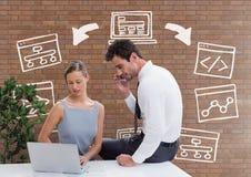 Executivos em uma mesa que olha um computador contra a parede de tijolo com gráficos Imagem de Stock