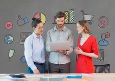 Executivos em uma mesa que olha uma tabuleta contra o fundo cinzento com gráficos Fotos de Stock Royalty Free
