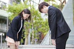 Executivos empresariais asiáticos novos que curvam-se entre si Foto de Stock Royalty Free