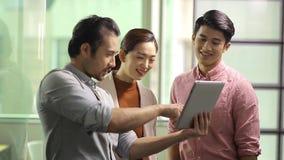 Executivos empresariais asiáticos que discutem o negócio no escritório filme