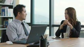 Executivos empresariais asiáticos que discutem o negócio no escritório