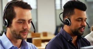 Executivos empresariais com auriculares usando o computador filme