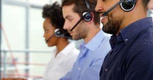 Executivos empresariais com auriculares usando o computador vídeos de arquivo