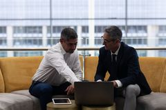 Executivos empresariais dos Caucasians que falam a discussão sobre o portátil ao sentar-se no sofá imagem de stock