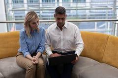 Executivos empresariais dos Caucasians que usam o portátil no sofá imagem de stock