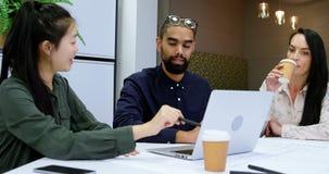 Executivos empresariais que discutem sobre um portátil 4k video estoque