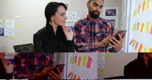 Executivos empresariais que discutem sobre uma tabuleta digital 4k video estoque