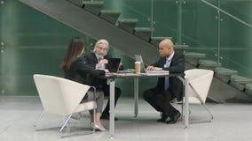 Executivos empresariais que encontram-se na entrada do prédio de escritórios moderno