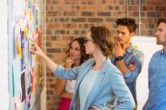 Executivos empresariais que olham notas pegajosas no whiteboard Foto de Stock