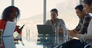 Executivos empresariais que sentam-se na tabela e que trabalham no escritório moderno 4k vídeos de arquivo