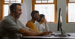 Executivos empresariais que trabalham com os auriculares na mesa 4k filme