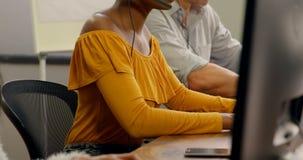 Executivos empresariais que trabalham com os auriculares na mesa 4k video estoque