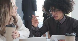 Executivos empresariais que usam a tabuleta e a calculadora digitais na reunião do escritório video estoque
