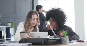 Executivos empresariais que usam a tabuleta e a calculadora digitais no escritório video estoque