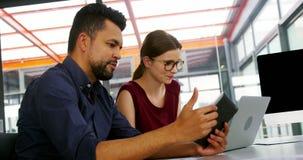 Executivos empresariais que usam a tabuleta e o portátil digitais video estoque