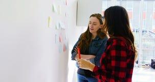 Executivos fêmeas que discutem sobre notas pegajosas video estoque