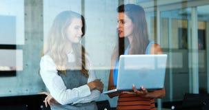 Executivos fêmeas que discutem sobre o portátil 4k vídeos de arquivo