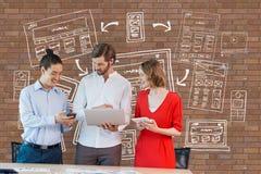 Executivos felizes em uma mesa que olha o computador e as tabuletas contra a parede de tijolo com gráficos Foto de Stock